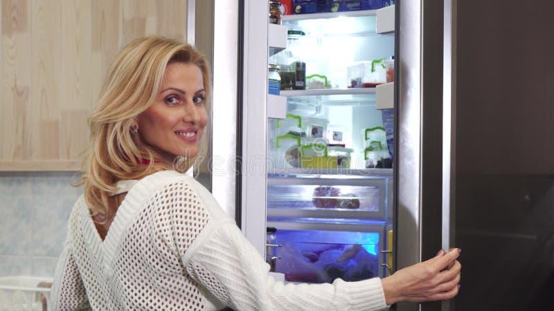 Ursnygg kvinna som ler till kameran som öppnar kylen på köket royaltyfri bild