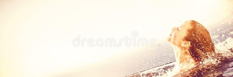 Ursnygg kvinna som lyfter hennes huvud ut ur vatten arkivfoton