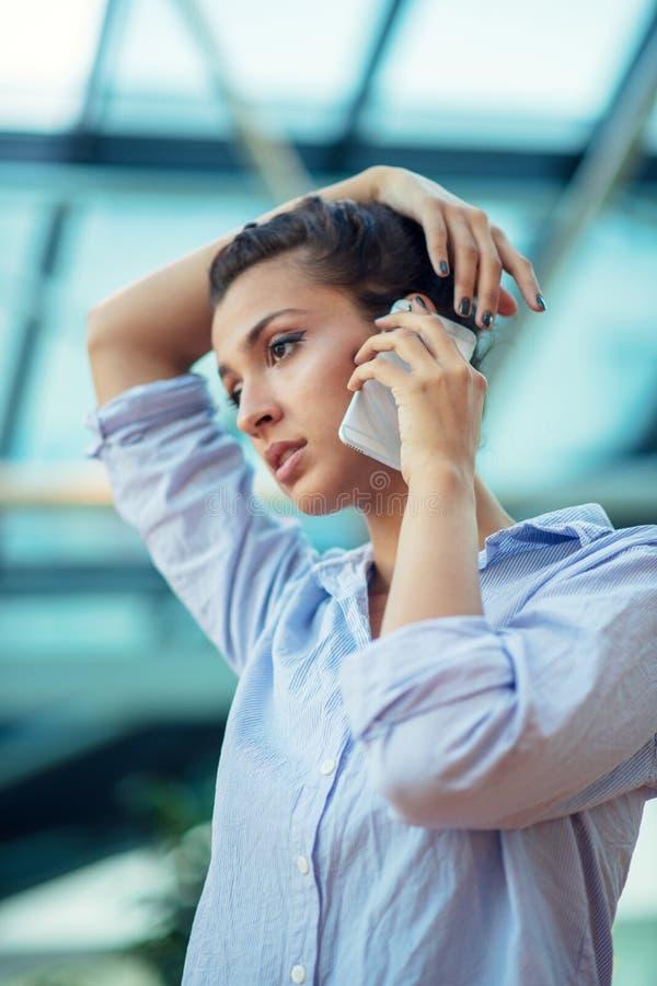 Ursnygg kvinna som talar p? mobiltelefonen p? flygplatsen royaltyfria foton
