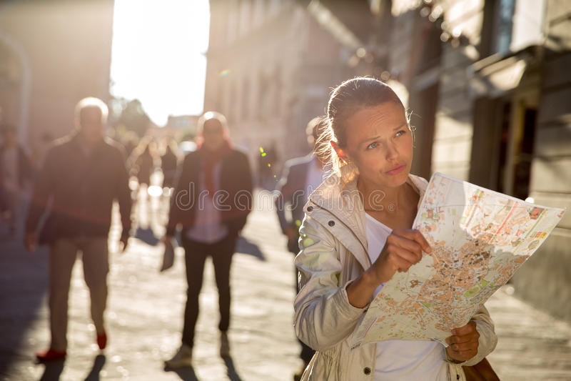 Ursnygg kvinnlig turist med en översikt som upptäcker en utländsk stad fotografering för bildbyråer