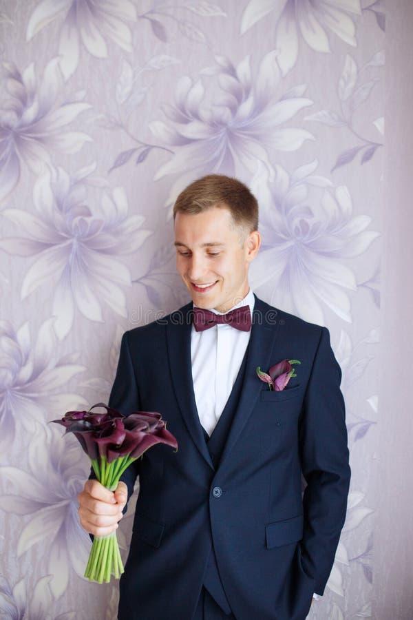 Ursnygg le brudgum Stilig brudgum på den le och väntande på bruden för bröllopsmoking Elegant man i svart dräkt och fluga royaltyfria foton