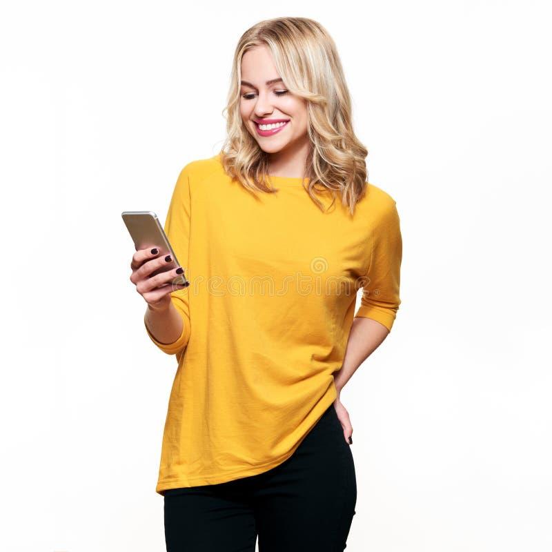 Ursnygg le kvinna som ser hennes mobiltelefon Kvinna som smsar på hennes telefon som isoleras över vit royaltyfri foto