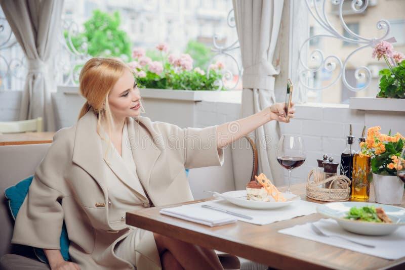 Ursnygg le självstående för blond kvinnadanande med mobiltelefonkameran, medan sitta i modernt kafé inom, charmig lycklig fe arkivfoton