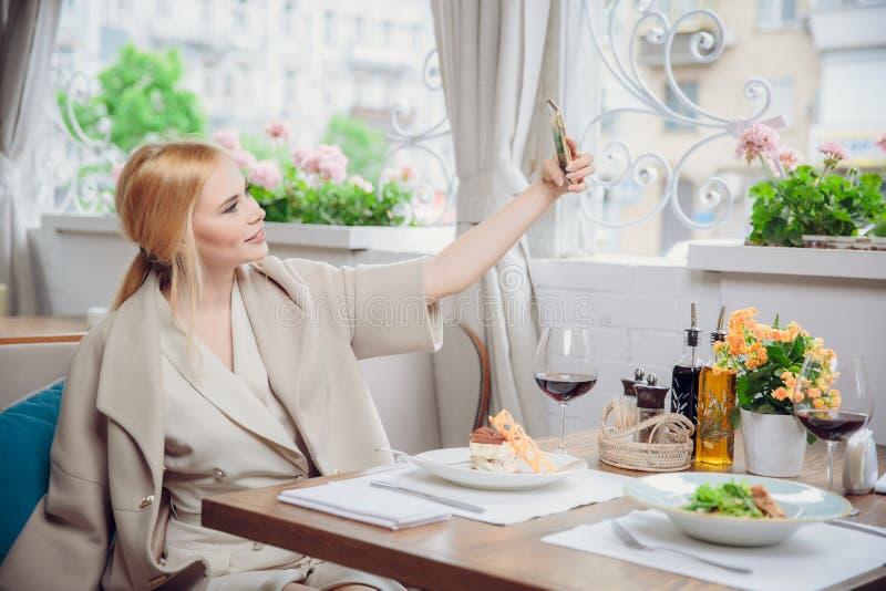 Ursnygg le självstående för blond kvinnadanande med mobiltelefonkameran, medan sitta i modernt kafé inom, charmig lycklig fe fotografering för bildbyråer