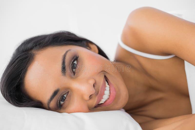Ursnygg lugna kvinna som ligger under räkningen på hennes säng arkivbilder