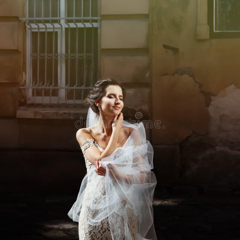 Ursnygg lycklig le brunettbrud i vitt klänningpos. för tappning royaltyfri fotografi