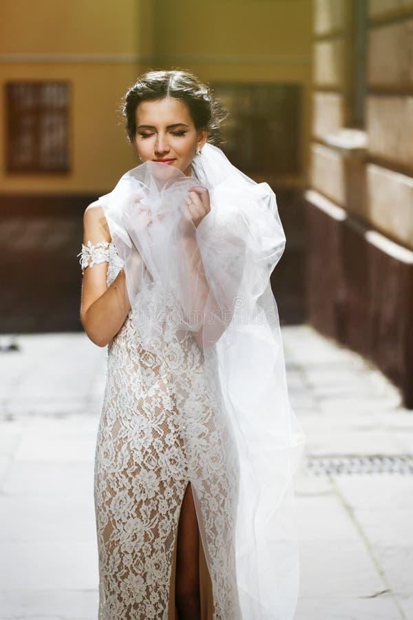 Ursnygg lycklig le brunettbrud i vitt klänningpos. för tappning arkivfoto