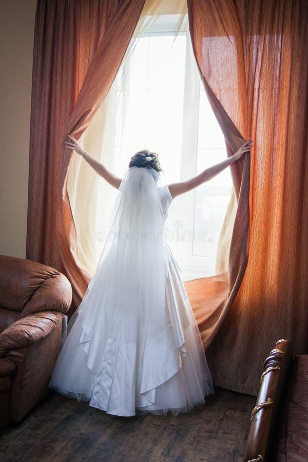 Ursnygg lycklig lyxig stilfull brunettbrud nära ett fönster arkivfoton