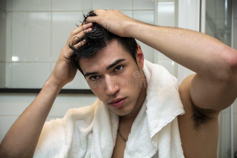Ursnygg man efter hans dusch som rymmer hans huvud royaltyfri foto