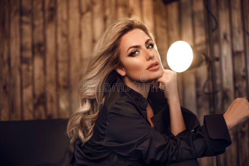 ursnygg modell Blond kvinnastående i svart skjorta Trendig flicka med skönhetmakeup och stil för lockigt hår som poserar i trä arkivbilder