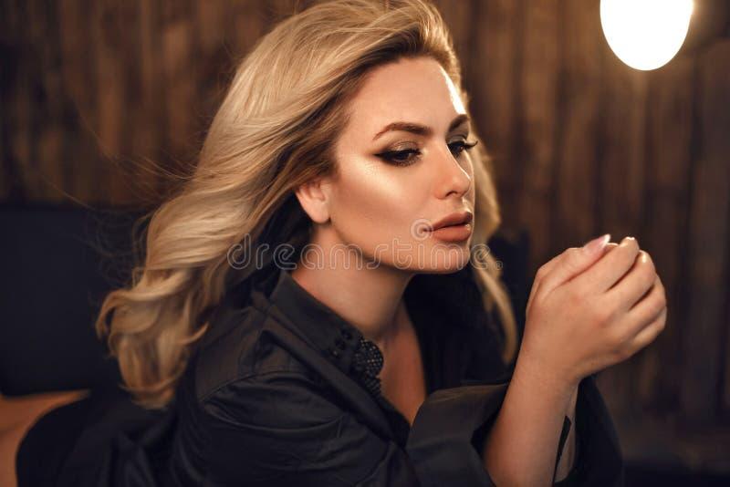 ursnygg modell Blond kvinnastående i svart skjorta Trendig flicka med skönhetmakeup och stil för lockigt hår som poserar i trä royaltyfria bilder