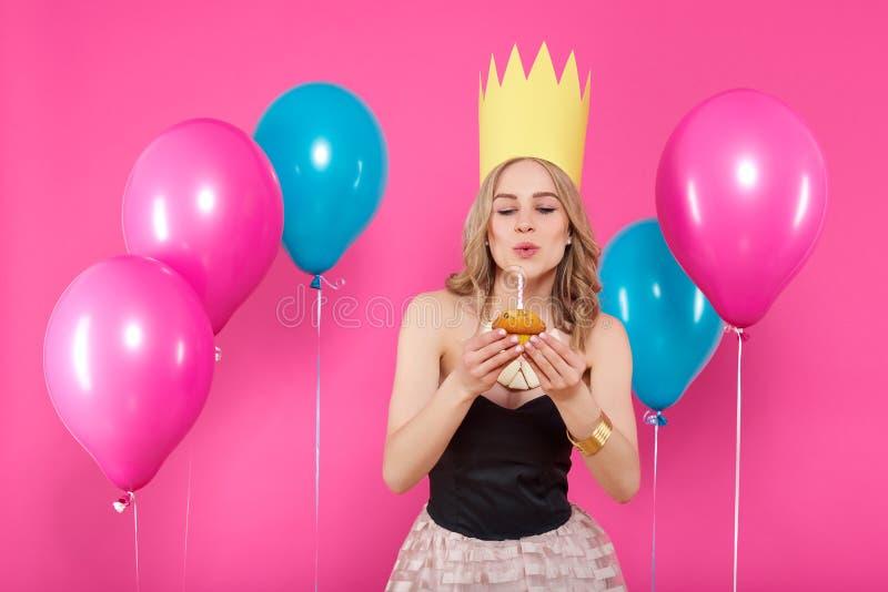 Ursnygg moderiktig ung kvinna i partidräkt och födelsedagkrona som ut blåser stearinljuset på hennes födelsedagmuffin Champagne m royaltyfria bilder