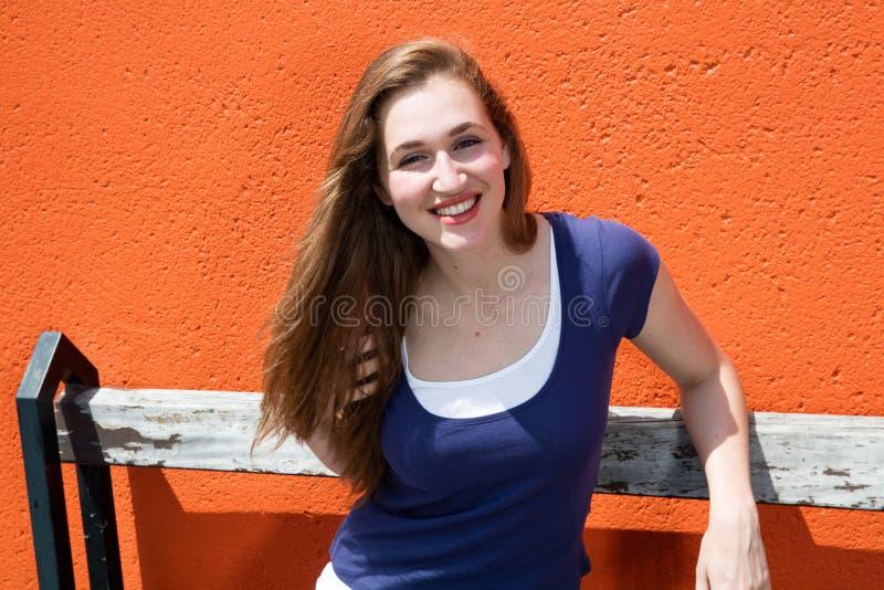 Ursnygg naturlig ung kvinnlig student som ler över en orange vägg arkivbilder