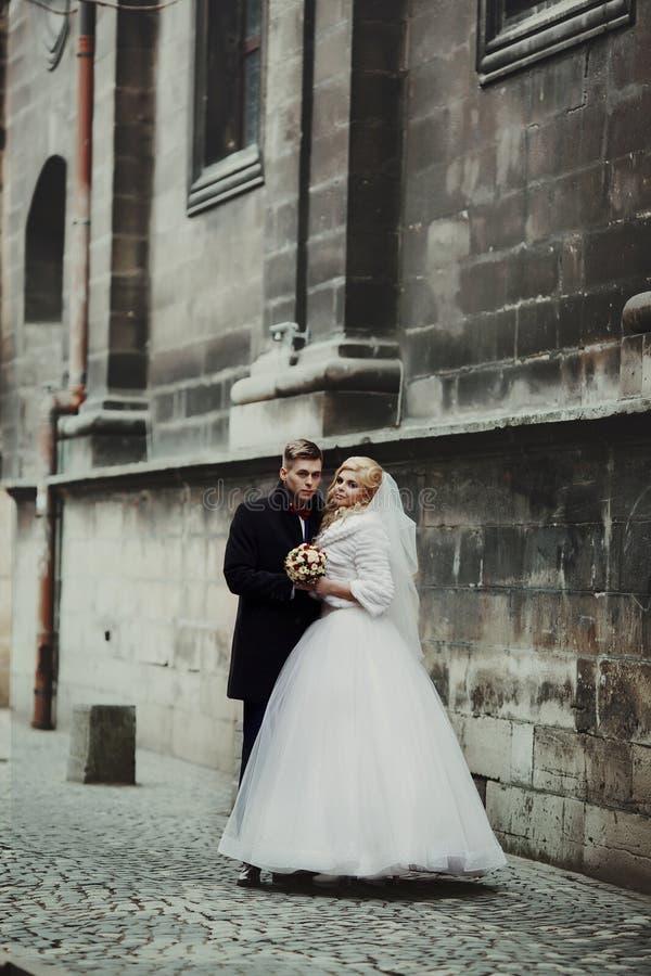 Ursnygg nygift personbrud i det vita den valenty laget och stiliga brudgummen royaltyfri foto