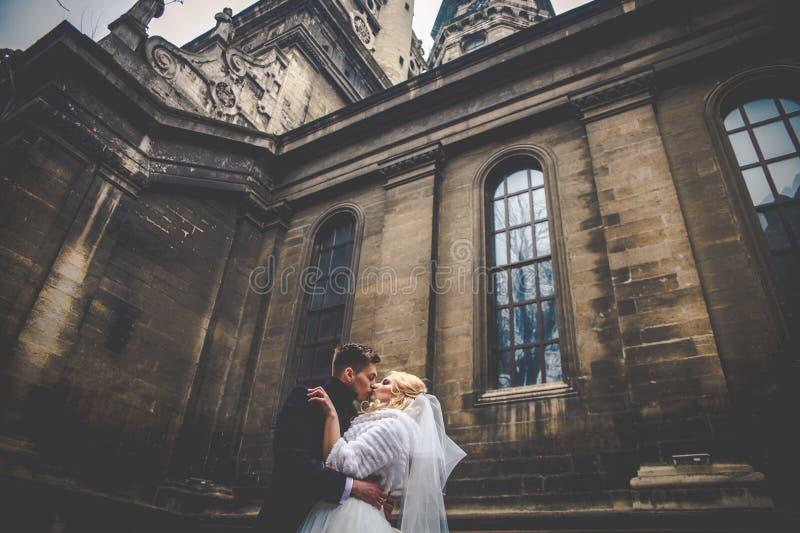 Ursnygg nygift personbrud i det vita den valenty laget och stiliga brudgummen arkivfoto