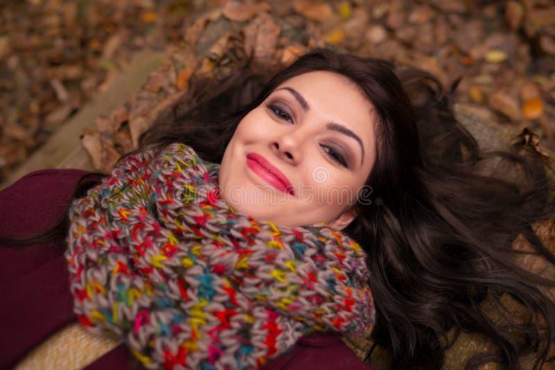 Ursnygg romantisk ung kvinna med härligt långt brunt hår som ner ligger i höstskogen, le som är lyckligt på arkivbild