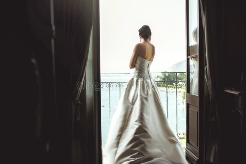 Ursnygg sexig brunettbrud som poserar på balkongen på den varma havssemesterorten royaltyfria bilder