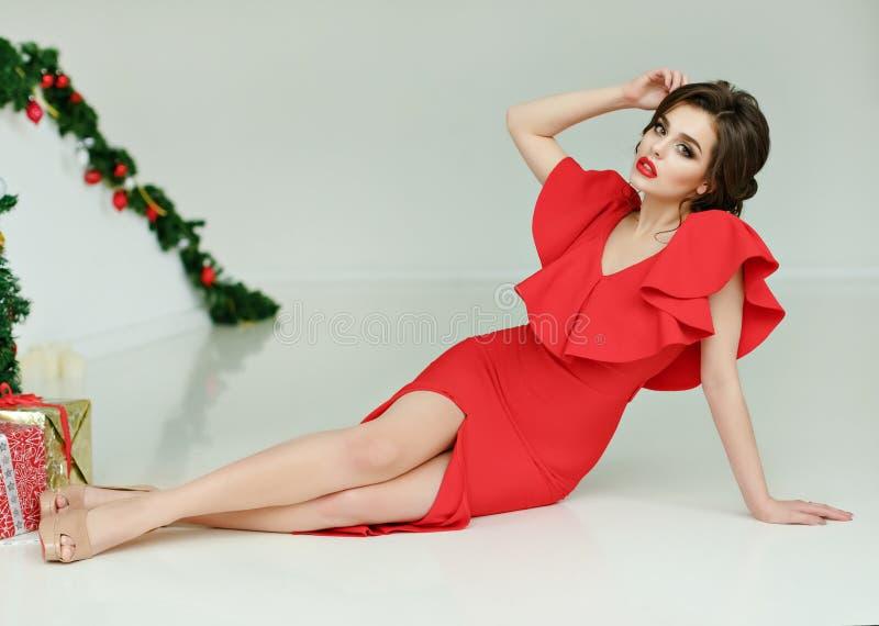 Ursnygg sexig brunettflicka i den röda klänningen, studio Jul royaltyfri foto
