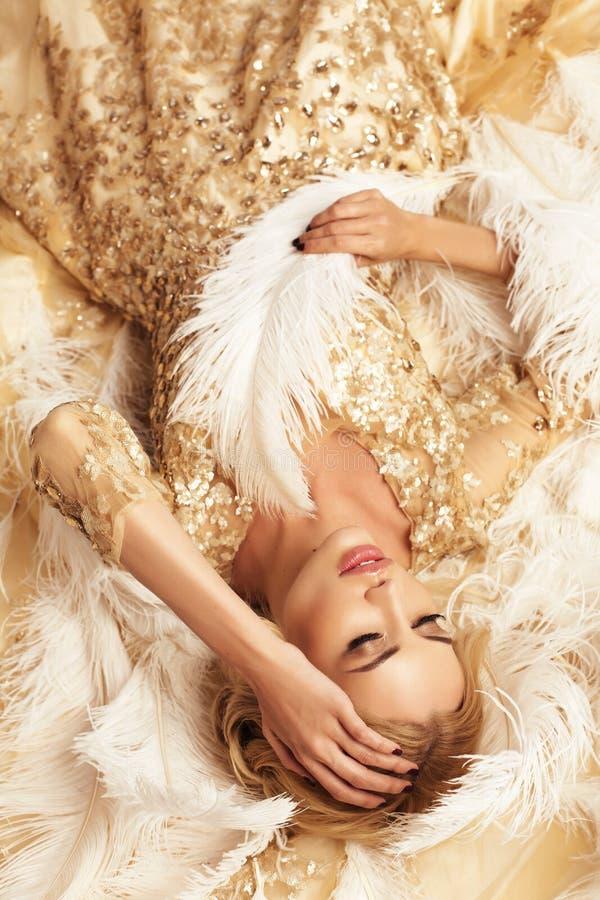 Ursnygg sexig kvinna med blont hår i lyxig beige klänning royaltyfri foto