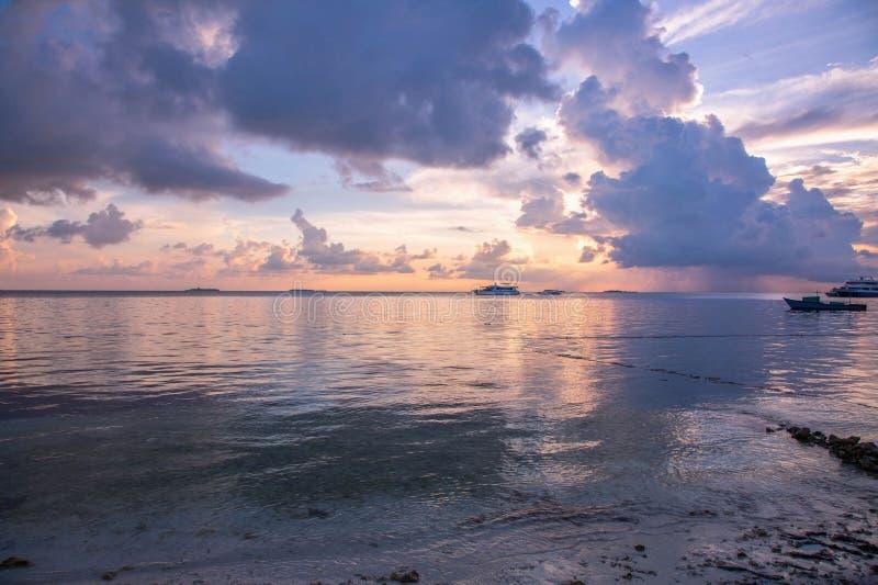 Ursnygg sikt av solnedgången på Indiska oceanen, blått vatten och blå himmel med vita moln Fantastiska naturbakgrunder arkivbilder