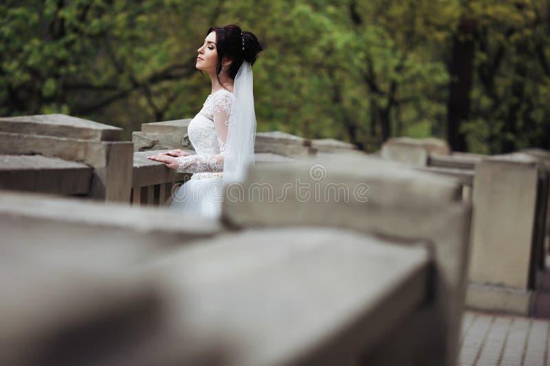 Ursnygg sinnlig brunettbrud i den vita klänningen som poserar på gammal st royaltyfri bild