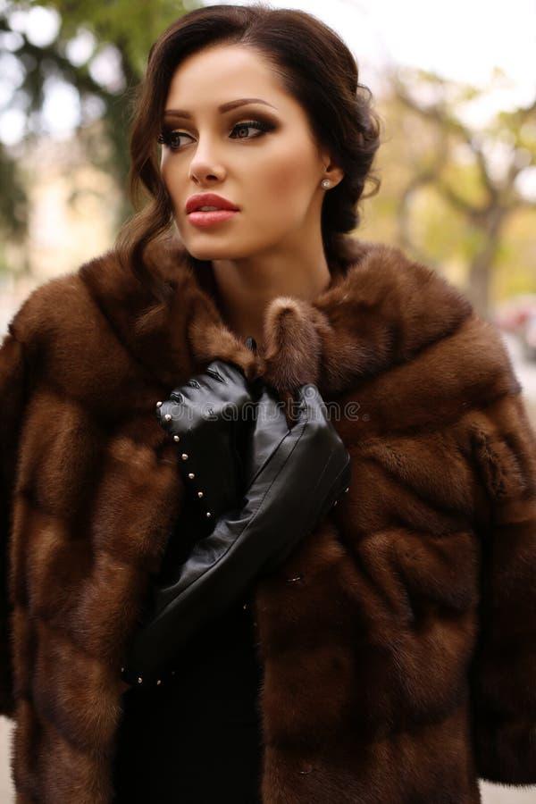 Ursnygg sinnlig kvinna med mörkt hår i lyxiga handskar för pälslag och läder royaltyfri foto