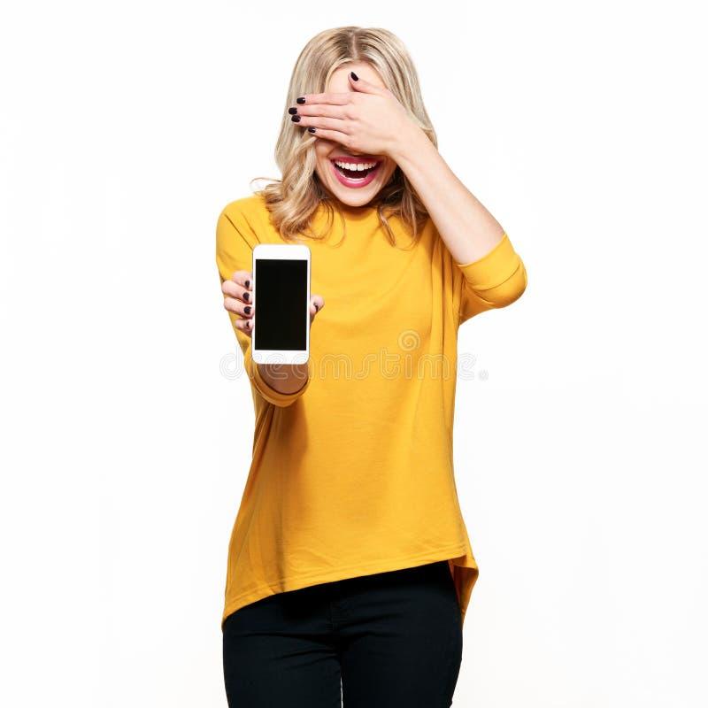 Ursnygg skratta kvinna som visar mobiltelefonen för tom skärm över vit bakgrund som täcker henne ögon med handen spännande mycket fotografering för bildbyråer
