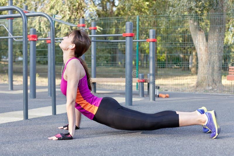 Ursnygg slank övningsyoga för ung kvinna på utomhus- sportsground Kobraasana Lugn och att koppla av och att sträcka Morgon för ve arkivbild