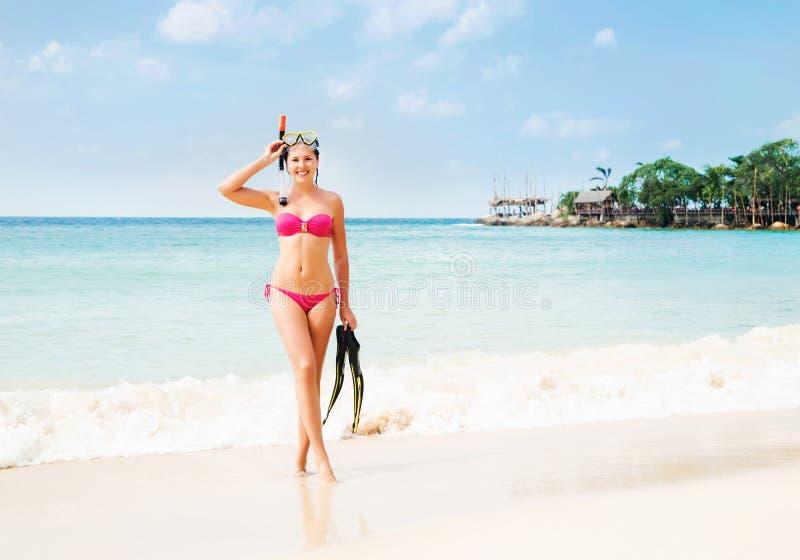 Ursnygg, slank gladlynt flicka som poserar med dykningmaskeringen, och flipper på seacoasten i Thailand fotografering för bildbyråer