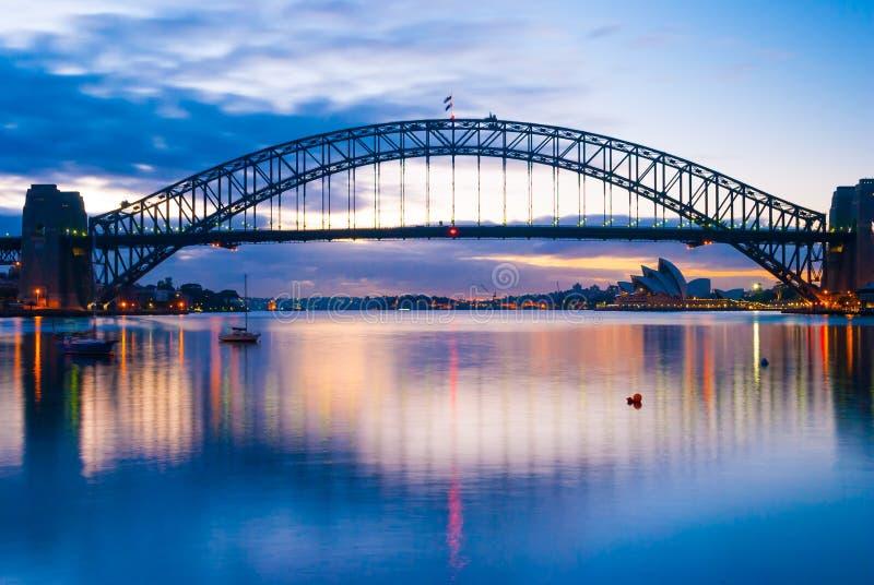 Ursnygg solnedgång på den väldiga stålSydney Harbor bron som korsar havet arkivfoton