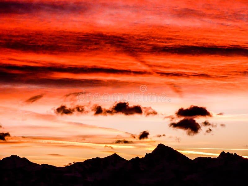 Ursnygg solnedgånghimmel över ojämn berglandskapkontur royaltyfria foton