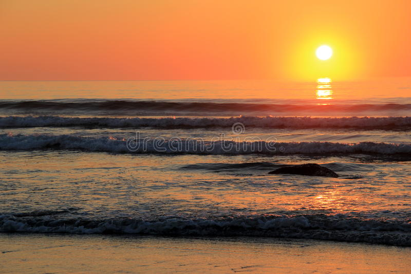 Ursnygg soluppgång över vaggar längs kusten fotografering för bildbyråer