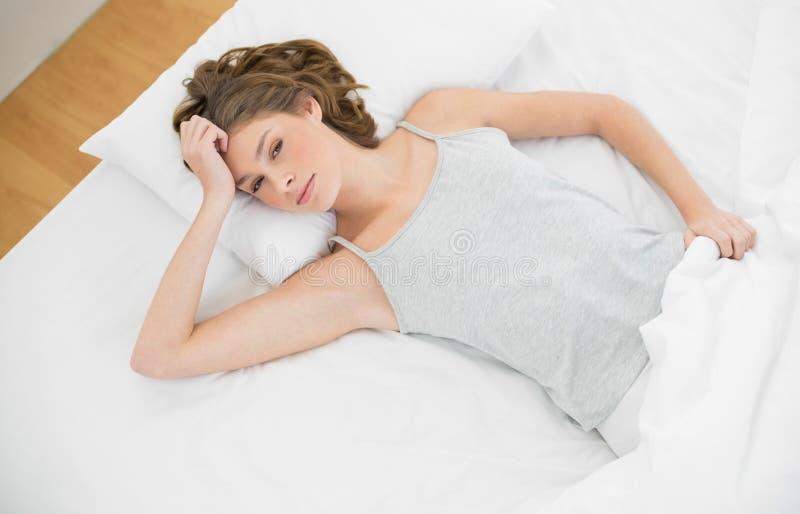Ursnygg spenslig kvinna som ligger på hennes säng under räkningen arkivfoton