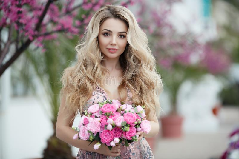 Ursnygg stående av en blond flicka i en sexig rosa klänning för afton med en bukett av härliga rosor fotografering för bildbyråer