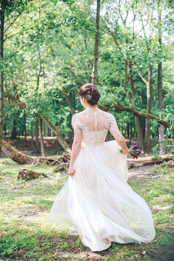 Ursnygg stilfull brud i den vita klänningen för tappning som går i parkera Härlig bröllopbrudspring i skogen fotografering för bildbyråer