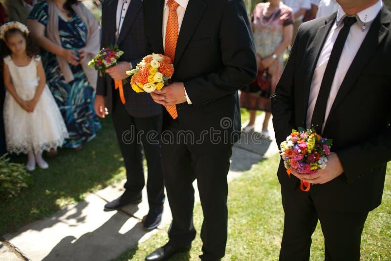 Ursnygg stilfull elegant brudgum och bästa man som rymmer färgrik bou royaltyfria bilder