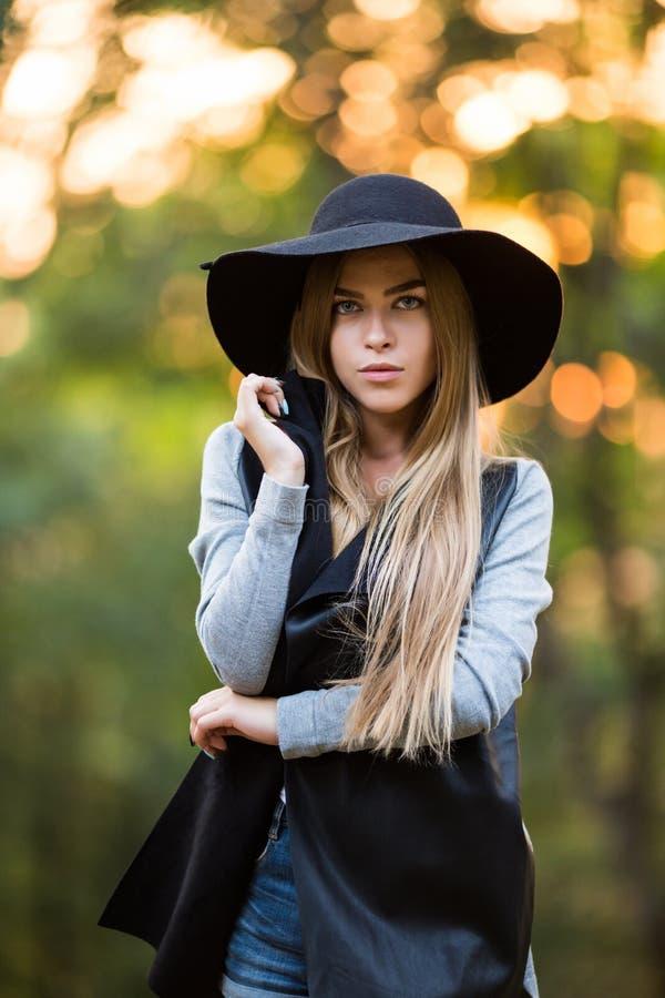 Ursnygg stilfull ung kvinna som bär trendig kläder arkivfoto