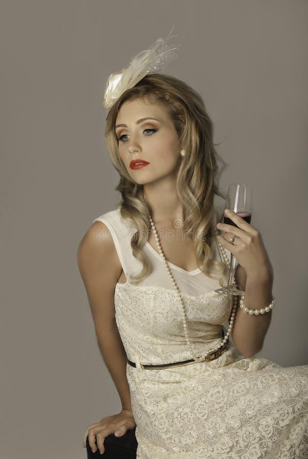 Ursnygg 50-talkvinna med fascinator och champagne arkivbild