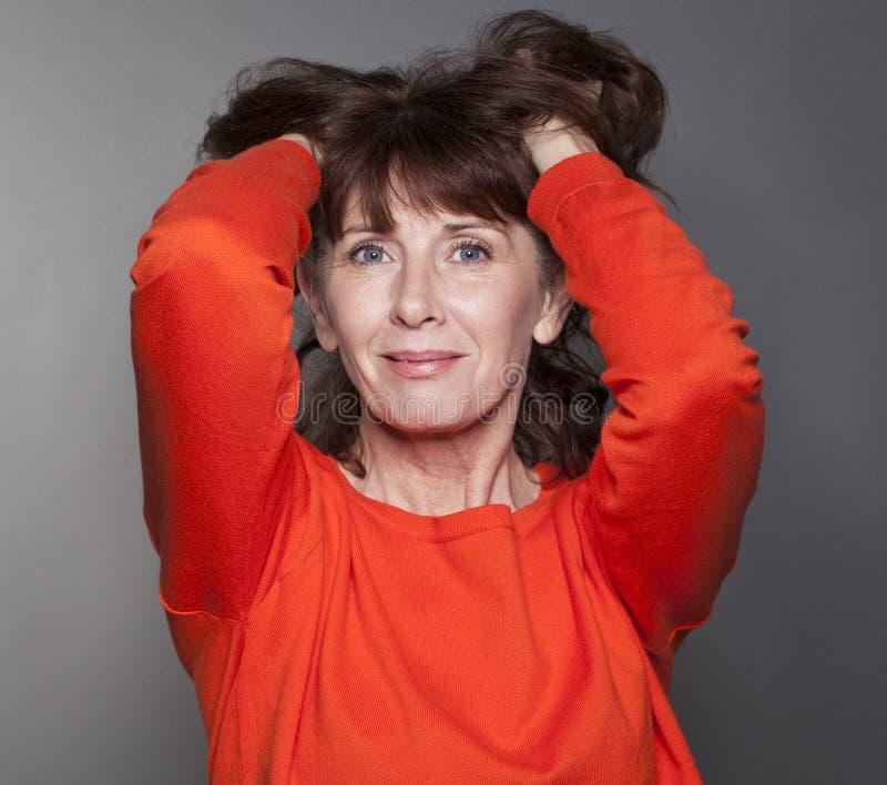 Ursnygg 50-talkvinna som trycker på hennes hår för tillfredsställelse royaltyfria foton