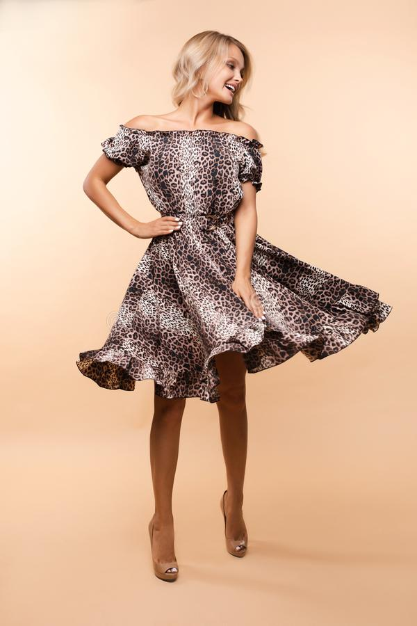 Ursnygg trendig dam i den stilfulla klänningen som vrider i studio arkivbild
