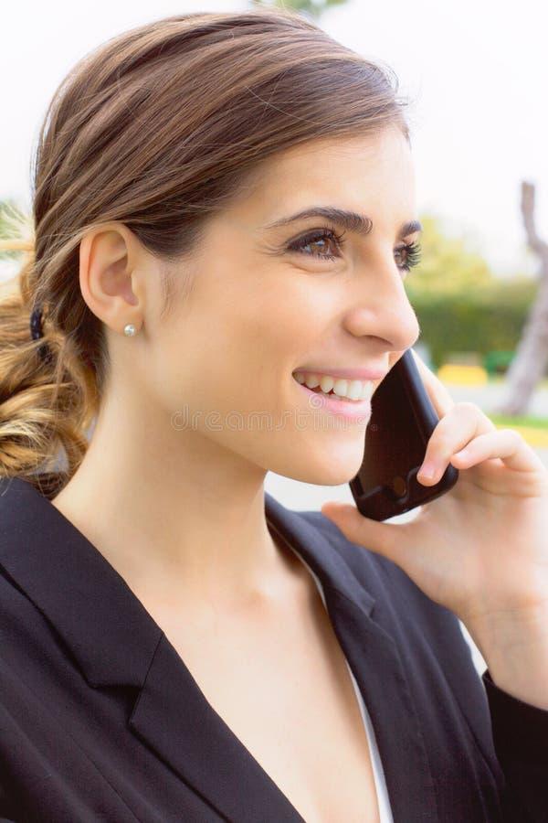 Ursnygg ung affärskvinna som ler samtal på telefoncloseupen arkivfoton