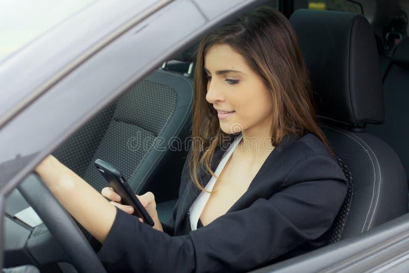 Ursnygg ung affärskvinna som ler samtal på telefonen i bil royaltyfria foton