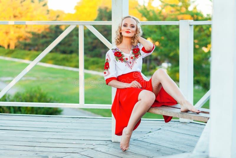 Ursnygg ung blond kvinna med makeup, lockig frisyr i den stilfulla röda vita klänningen som poserar på bänk i trädgårdaxel sitta  fotografering för bildbyråer