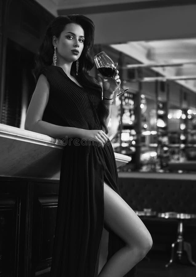 Ursnygg ung brunettkvinna i mörk klänning med vin royaltyfria bilder