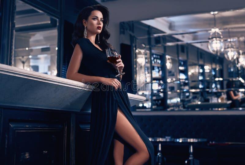 Ursnygg ung brunettkvinna i mörk klänning med vin fotografering för bildbyråer