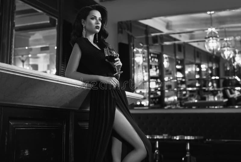 Ursnygg ung brunettkvinna i mörk klänning med vin arkivfoton