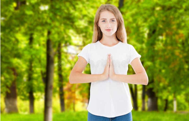 Ursnygg ung Caucasian kvinnlig som bär hennes ingefära och att rymma händer i namaste eller bönen som håller ögon öppnade, medan  arkivbilder