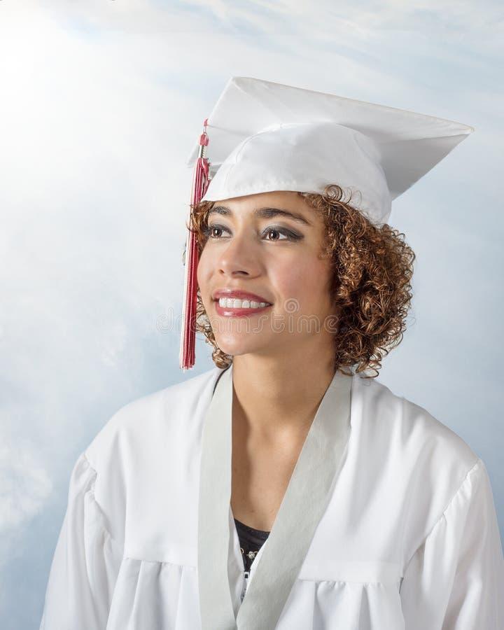 Ursnygg ung dam för blandat lopp med lockigt brunt hår i ett vit lock och kappa med den röda och vita tofsen arkivfoton