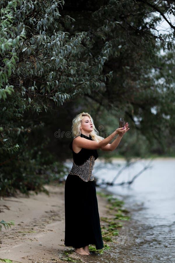 Ursnygg ung kvinna i lång svart klänning på stranden royaltyfria bilder