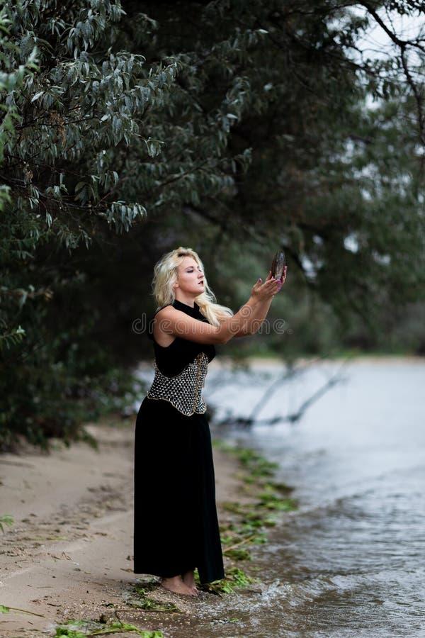 Ursnygg ung kvinna i lång svart klänning på stranden royaltyfria foton